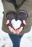 Mains femelles jugeant un coeur fabriqué à partir de la neige Photos stock