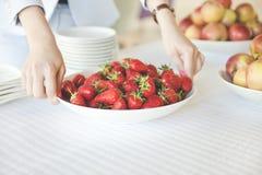 Mains femelles jugeant un plat plein des fraises images stock
