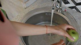Mains femelles lavant deux pommes vertes Delicious dans l'eau banque de vidéos