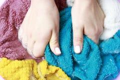 Mains femelles lavant les vêtements multicolores en bassin, vue supérieure photo stock