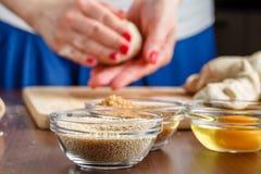 Mains femelles malaxant la pâte sur la table en bois image libre de droits