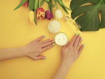 Mains femelles manucure, crème, fleur de tulipe sur un fond jaune image libre de droits