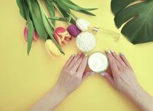 Mains femelles manucure, crème hydratante de crème, bien-être de produits de fleur de tulipe de mode de vie sur un fond jaune images stock