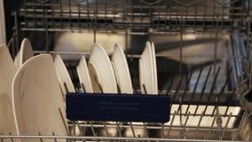 Mains femelles mettant de grands et petits plats blancs dans le lave-vaisselle clips vidéos