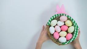 Mains femelles mettant le panier actuel de Pâques sur la table, oeufs colorés, cadeau fait main banque de vidéos