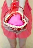 Mains femelles offrant le coeur rose dans le petit panier tricoté Photos libres de droits