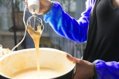 Mains femelles remuant la pâte avec un mélangeur pour le gâteau ou le pain dans une cuvette sur un plan de travail de cuisine, pr Photo stock