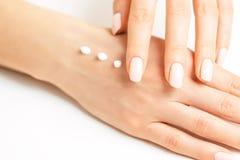 Mains femelles s'appliquant hydratant la crème pour la peau lisse photographie stock libre de droits