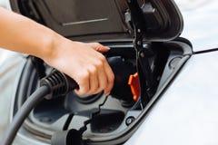 Mains femelles savoureuses chargeant une voiture électrique Photos stock