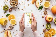 Mains femelles se tenant utilisant le smartphone sur le fond sain de nourriture photo libre de droits