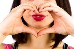 Mains femelles sous forme de coeur sur le fond d'un sourire Image stock