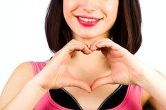 Mains femelles sous forme de coeur sur le fond d'un sourire Photo stock