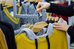 Mains femelles sur le contact un cintre de manteau avec des vêtements dans la boutique photo libre de droits
