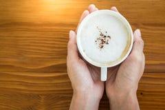 Mains femelles tenant des tasses de café sur la table en bois Image stock