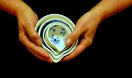Mains femelles tenant des tasses de mesure de porcelaine Image libre de droits