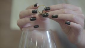 Mains femelles tenant l'anneau l'épousant d'or sous le verre de vin blanc L'alcool potable de femme en raison de la famille clips vidéos