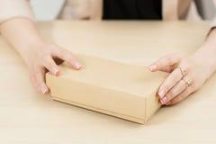 Mains femelles tenant la boîte de carton sur la table image stock