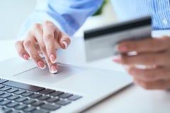 Mains femelles tenant la carte de crédit et dactylographiant des nombres sur le clavier d'ordinateur portable tout en se reposant photos stock