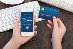Mains femelles tenant la carte de crédit et le téléphone dans le bureau et les valeurs maximales de concentration au poste de trav images stock