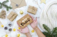 Mains femelles tenant la carte de voeux fabriquée à la main de Joyeux Noël avec le lettrage de main Vacances de Noël Composition  photographie stock