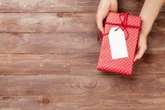 Mains femelles tenant le cadeau au-dessus de la table en bois images libres de droits