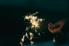 Mains femelles tenant le cierge magique avec le fond de nuit Images stock