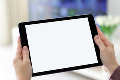 Mains femelles tenant le comprimé d'ordinateur avec l'écran d'isolement dans le roo Image libre de droits