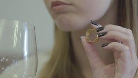 Mains femelles tenant le plan rapproché d'anneau l'épousant d'or et en verre de vin L'alcool potable de jeune femme en raison de  clips vidéos
