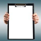 Mains femelles tenant le presse-papiers médical avec la page du papier blanche Photo stock