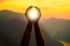 Mains femelles tenant le soleil le jour ensoleillé d'été Images libres de droits
