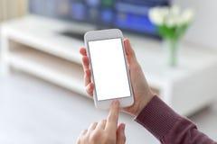 Mains femelles tenant le téléphone avec l'écran d'isolement dans la chambre Photographie stock libre de droits
