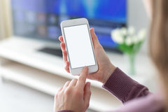 Mains femelles tenant le téléphone avec l'écran d'isolement dans la chambre Photo libre de droits