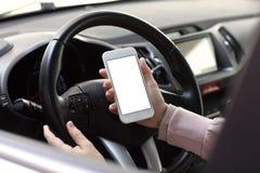 Mains femelles tenant le téléphone avec l'écran d'isolement derrière la voiture de roue Images stock