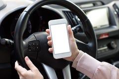 Mains femelles tenant le téléphone avec l'écran d'isolement derrière la voiture de roue Photographie stock libre de droits