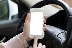 Mains femelles tenant le téléphone avec l'écran d'isolement derrière la voiture de roue Photographie stock