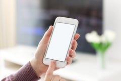 Mains femelles tenant le téléphone avec l'écran dans la chambre Images libres de droits
