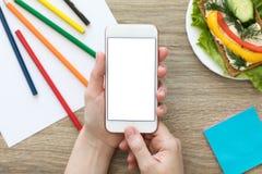 Mains femelles tenant le téléphone avec l'écran dans le CAM coloré Image libre de droits