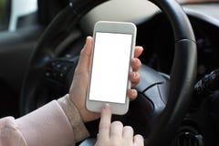 Mains femelles tenant le téléphone avec l'écran derrière la voiture de roue Photographie stock libre de droits