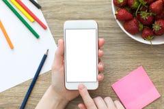 Mains femelles tenant le téléphone blanc avec l'écran d'isolement Photographie stock