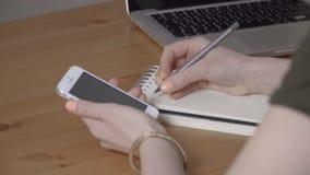 Mains femelles tenant le téléphone blanc et écrivant quelque chose sur le carnet clips vidéos