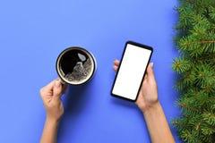Mains femelles tenant le téléphone portable noir avec l'écran et la tasse blancs vides de café Image de maquette avec l'espace de images libres de droits