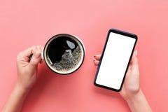 Mains femelles tenant le téléphone portable noir avec l'écran et la tasse blancs vides de café Image de maquette avec l'espace de photos libres de droits