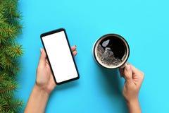 Mains femelles tenant le téléphone portable noir avec l'écran et la tasse blancs vides de café Image de maquette avec l'espace de photos stock