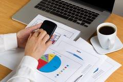 Mains femelles tenant le téléphone portable tout en regardant le diagramme financier photos stock
