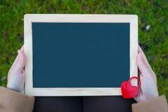 Mains femelles tenant le tableau noir avec le cadenas rouge en forme de coeur Photo stock