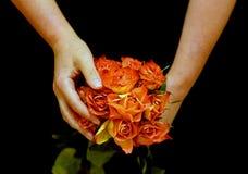 Mains femelles tenant les roses jaunes Photos stock