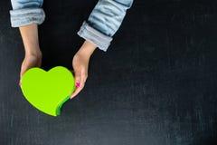 Mains femelles tenant une boîte sous forme de coeur avec un présent Photographie stock