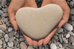 Mains femelles tenant une pierre en forme de coeur image libre de droits