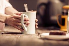 Mains femelles tenant une tasse blanche de thé se tenant près du bureau en bois Image stock