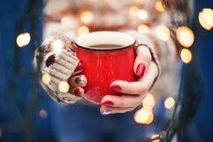 Mains femelles tenant une tasse Carte d'an neuf ou de Noël Photographie stock libre de droits
